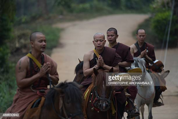 ThailandreligiondrugssocialFEATURE by Marion THIBAUT This picture taken on April 8 2015 shows horseriding monks praying after they were offered alms...