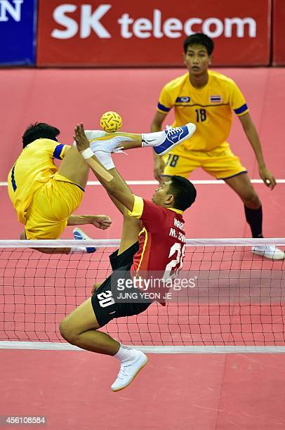 Thailand's Anuwat Chaichana challenges for the ball with Malaysia's Mohd Zamree Bin Mohd Dahan in the men's team sepaktakraw semifinal match during...