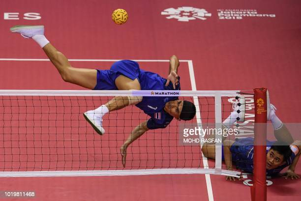 TOPSHOT Thailand's Anuwat Chaichana jumps for the ball as his teammate Assadin Wongyota looks on during the sepak takraw men's team regu match...