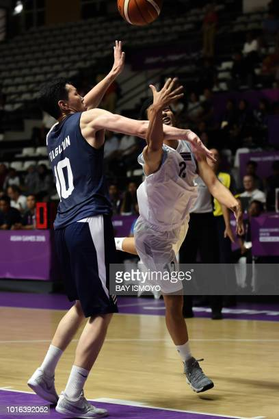 Thailand's Bandit Lakhan is challenged by Mongolia's Bilguun Battuvshin in their men's basketball preliminary Group A game between Thailand and...