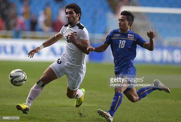 Thailand's Chanathip Songkrasin battles for the ball with Iraq's Al Mamoori Sameh Saeed Mejbel during the football men's bronze medal match of the...