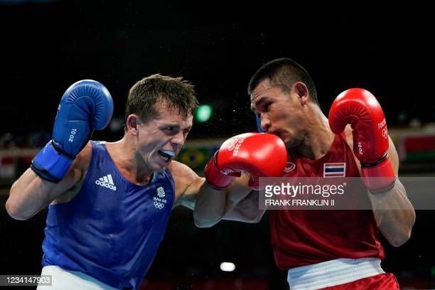 Thailand's Chatchai-Decha Butdee and Britain's Peter Mcgrail fight during their men's feather preliminaries boxing match during the Tokyo 2020...