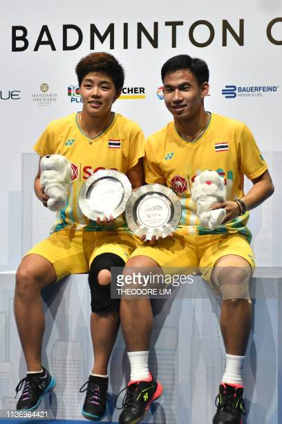 Thailand's Dechapol Puavaranukroh and Sapsiree Taerattanachai pose for photos after beating Malaysia's Tan Kian Meng and Lai Pei Jing in their mixed...