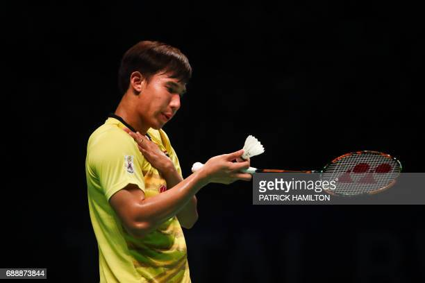 Thailand's Dechapol Puavaranukroh checks his racket during the men's doubles Sudirman Cup match with Bodin Issara against Seung Jae Seo and Choi...