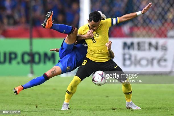 Thailand's defender Philip Roller and Malaysia's forward Zaquan Adha fight for the ball during the second leg of the AFF Suzuki Cup 2018 semifinal...