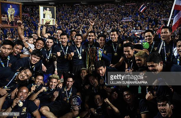 Thailand's football players and staff celebrate in front of a home crowd after winning the AFF Suzuki Cup final between Thailand and Indonesia 2-0 at...