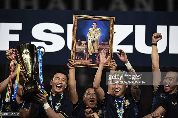 Thailand's football team players and staff hold aloft an image of Thai King Maha Vajiralongkorn after Thailand won the AFF Suzuki Cup Final between...
