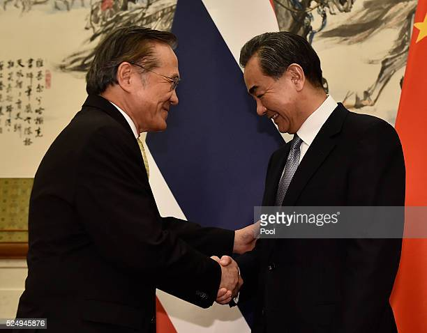 Thailand's Foreign Minister Don Pramudwinai shakes hands with Chinese Foreign Minister Wang Yi before a meeting at the Diaoyutai State Guesthouse on...