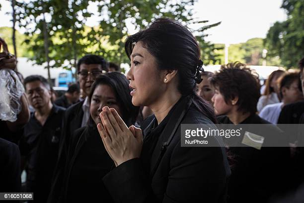 Thailand's former Prime Minister Yingluck Shinawatra greets supporters and mourners during her arrival at the Supreme Court in Chaeng Wattana...
