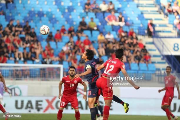 Thailand's forward Teerasil Dangda jumps for the ball against Bahrain's defender Ahmed Juma during the 2019 AFC Asian Cup group A football match...