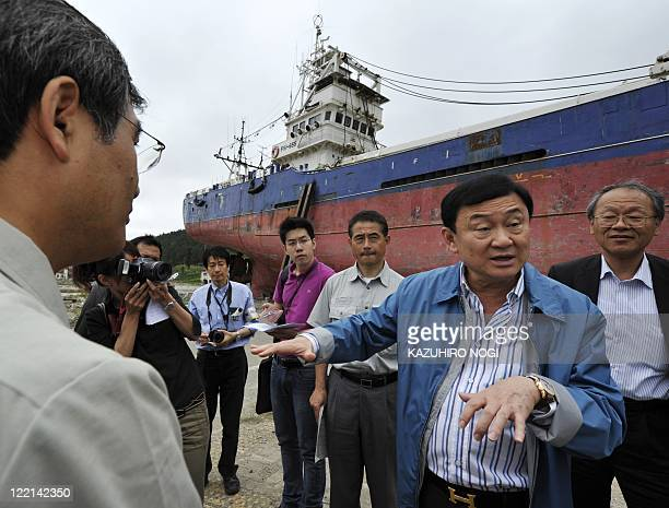 Thailand's fugitive ex-prime minister Thaksin Shinawatra talks with Kesennuma city vice mayor Keita Kato in front of a tsunami grounded fishing boat...