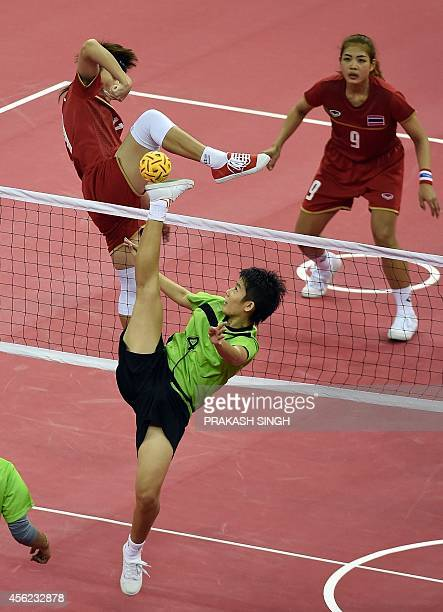 Thailand's Jankaen Wanwisa watches as Srihongsa Payom challenges for the ball with Myanmar's Khin Hnin Wai in the women's team sepaktakraw final...
