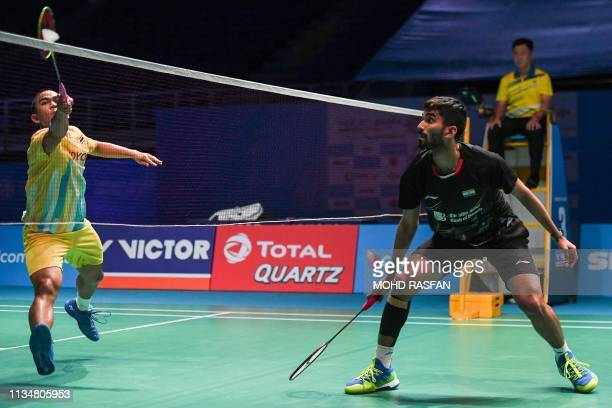 Thailand's Khosit Phetpradab hits a return against India's Kidambi Srikanth during their men's singles match at the Malaysia Open badminton...