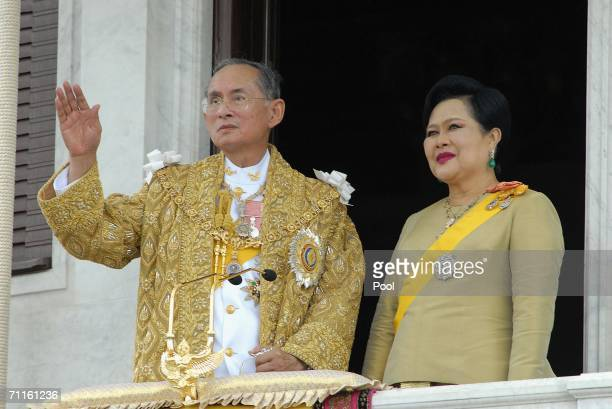 Thailand's King Bhumibol Adulyadej and Queen Sirikit wave to the thousands of people waiting outside the Royal Plaza to pay tribute to King Bhumibol...