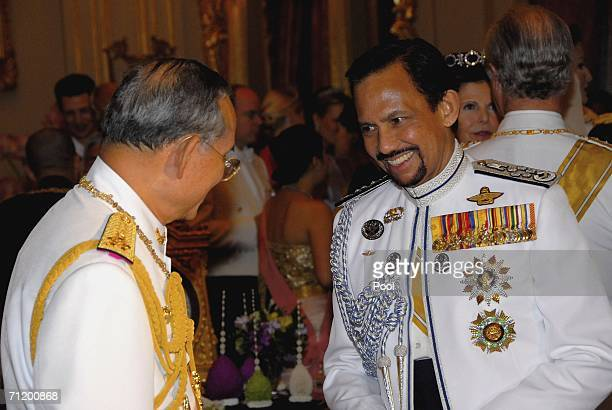 Thailand's King Bhumibol Adulyadej speaks with Sultan of Brunei as they attend the Royal banquet at the Golden Palace on June 13, 2006 in Bangkok,...
