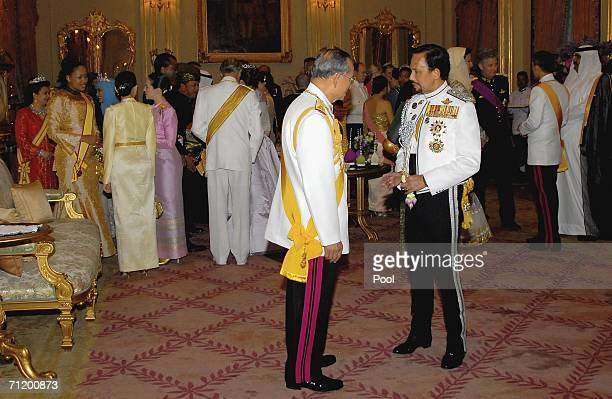 Thailand's King Bhumibol Adulyadej speaks with the Sultan of Brunei as they attend the Royal banquet at the Golden Palace on June 13, 2006 in...