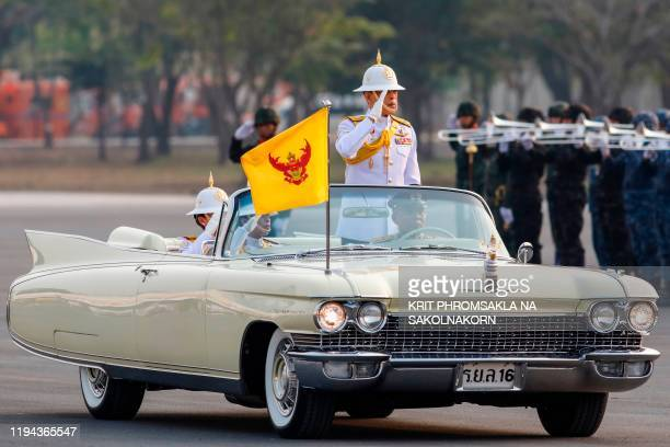 Thailand's King Maha Vajiralongkorn accompanied by Queen Suthida and Princess Bajrakitiyabha stands to salute while inspecting military troops during...