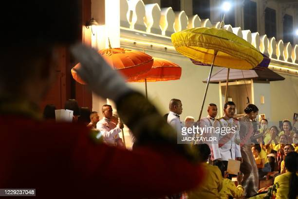 Thailand's King Maha Vajiralongkorn and Queen Suthida greet royalist supporters as they leave the Grand Palace after a Buddhist ceremony for the late...