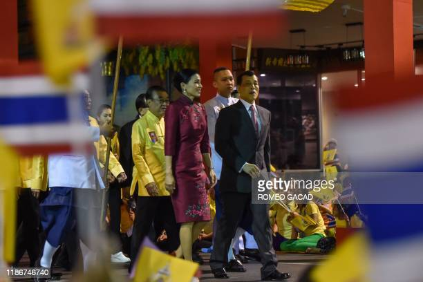 Thailand's King Maha Vajiralongkorn and Queen Suthida walk along the Yaowarat street during a visit to the Chinatown district of Bangkok, on December...
