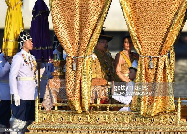 Thailand's King Maha Vajiralongkorn his wife Queen Suthida and Prince Dipangkorn Rasmijoti sit at the Royal barge during the Royal Barge procession...