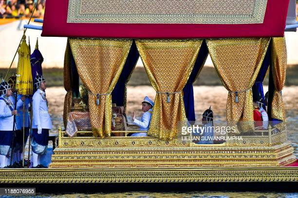 Thailand's King Maha Vajiralongkorn son Prince Dipangkorn Rasmijoti wave from the Royal barge during the Royal Barge procession in Bangkok on...