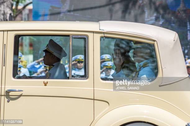 Thailand's King Maha Vajiralongkorn waves as he arrives with Queen Suthida at the Grand Palace for his coronation in Bangkok on May 4 2019