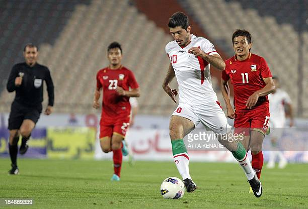 Thailand's Korrakot Wiriyaudomsiri fights for the ball with Karim Ansarifard of Iran during their 2015 Asian Cup group B qualifying football match at...