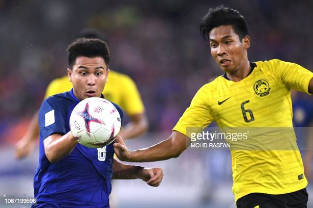 Thailand's midfielder Thitipan Puangchan and Malaysia's defender Syazwan Andik fight for the ball during the first leg of the AFF Suzuki Cup 2018...