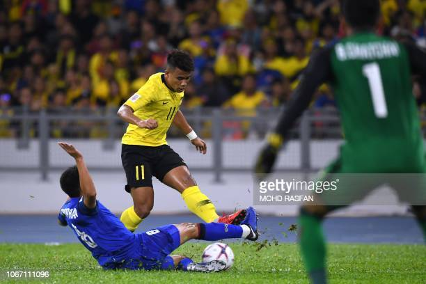 Thailand's midfielder Thitipan Puangchan and Malaysia's midfielder Safawi Rasid fight for the ball in front of Thailand's goalkeeper Chatchai Budprom...