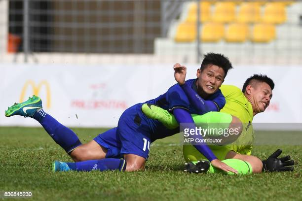 Thailand's Montree Promsawat crashes into the Philippines' goalkeeper Ray Joseph Joyel during their men's football match at the 29th Southeast Asian...