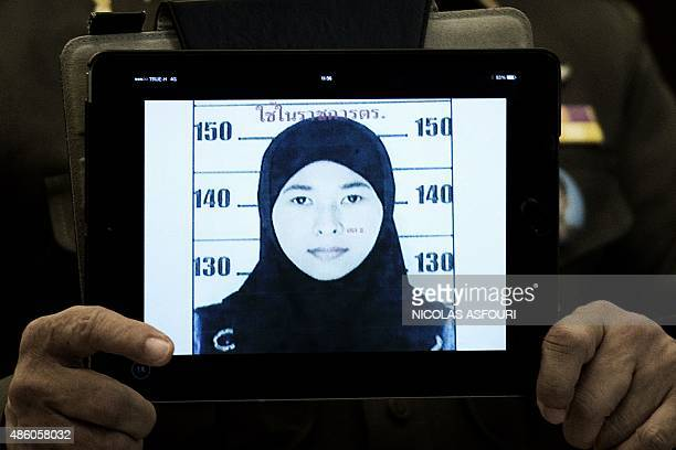 Thailand's national police spokesman Prawut Thavornsiri holds a tablet displaying a picture of Wanna Suansan wanted for questioning after bomb making...