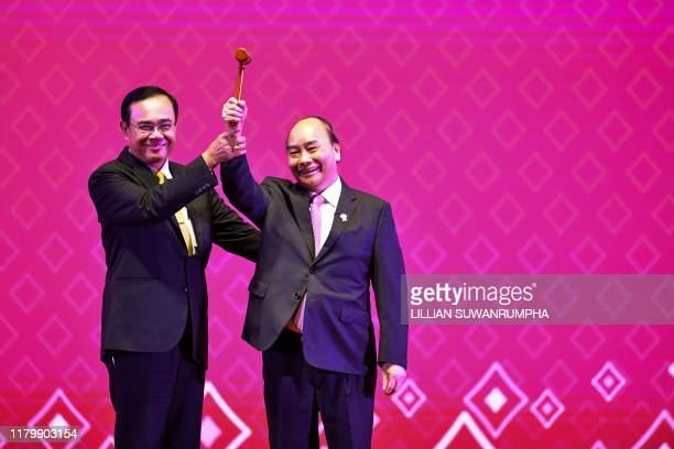 Thailand's Prime Minister Prayut ChanOCha hands the gavel for ASEAN chairmanship to Vietnam's Prime Minister Nguyen Xuan Phuc during the closing...