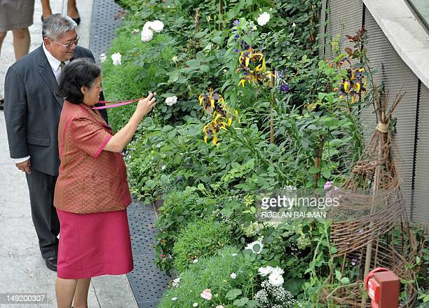 Thailand's Princess Maha Chakri Sirindhorn photographs a plat as Kiat W Tan CEO for Garden by the Bay looks on during a visit to the Garden by the...