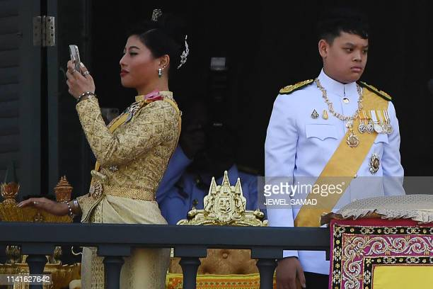 Thailand's Princess Sirivannavari Nariratana takes a photo as she stands with Prince Dipangkorn Rasmijoti during a public audience granted by...