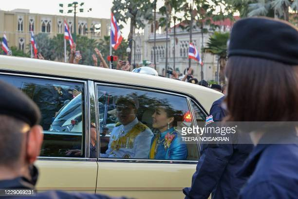 Thailand's Queen Suthida and Prince Dipangkorn Rasmijoti react inside a royal motorcade as it drives past a pro-democracy rally, as anti-government...