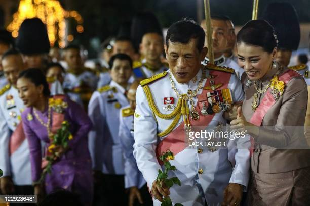 Thailand's Queen Suthida gestures to a royalist supporter beside King Maha Vajiralongkorn after a Buddhist ceremony for the late king Chulalongkorn...
