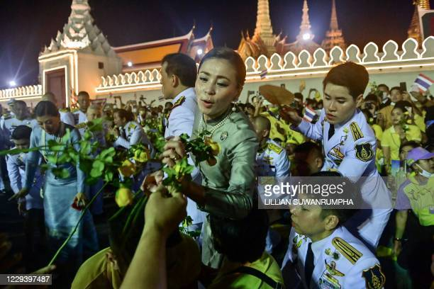 Thailand's Queen Suthida receives yellow roses beside King Maha Vajiralongkorn as they greet royalist supporters outside the Grand Palace in Bangkok...
