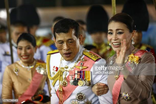 Thailand's Queen Suthida waves to royalist supporters beside King Maha Vajiralongkorn and Princess Sirivannavari Nariratana after a Buddhist ceremony...