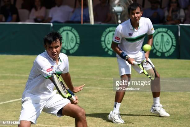 Thailand's Ratiwana Sanchai returns the ball to Pakistan's Muhammad Abid and Shahzadat Khan as teammate Ratiwana Sonchat looks on during their Davis...