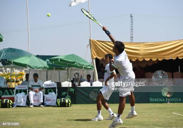 Thailand's Ratiwana Sonchat returns the ball to Pakistan's Muhammad Abid and Shahzadat Khan as teammate Ratiwana Sanchai looks on during their Davis...