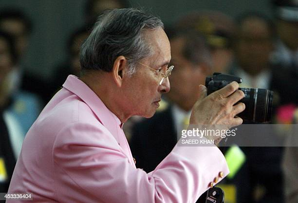 Thailand's revered King Bhumibol Adulyadej takes pictures of wellwishers as he prepares to leave Siriraj Hospital in Bangkok 07 November 2007 after...