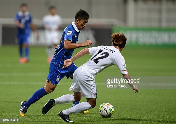 Thailand's Sarawut Masuk challenges Myanmar's Si Thu Aung during the AFF Suzuki 2014 Cup football match between Thailand and Myanmar at the Jalan...