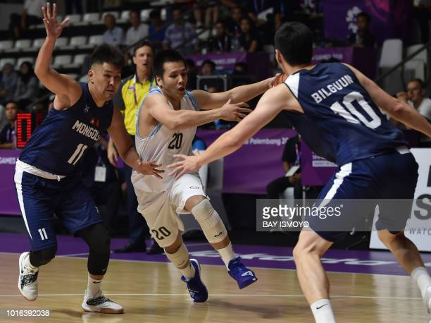 Thailand's Sirapong Boonyai is challenged by Mongolian players in their men's basketball preliminary Group A game between Thailand and Mongolia...