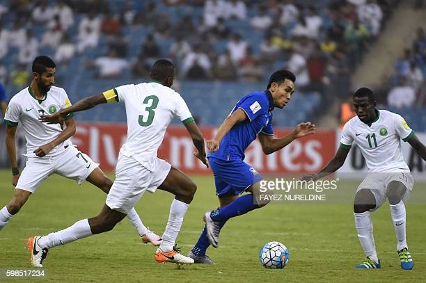 Thailand's Teerasil Dangda runs with the ball past Saudi Osama Hawsawi and teammates Salem Faraj and Abdulmalek Al Khaibri during their World Cup...