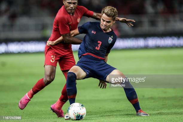 Thailand's Theerathon Bunmathan in action with Indonesia's Yustinus Paew during FIFA World Cup 2022 qualifying match between Indonesia and Thailand...