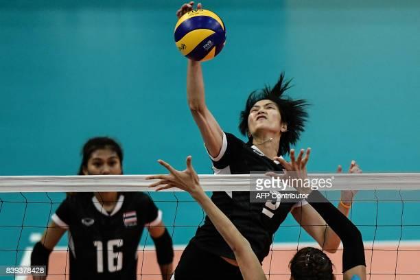 TOPSHOT Thailand's Thinkaow Pleumjit spikes the ball against Philippines player Santiago Alyja Daphne Antonio during their volleyball women's...