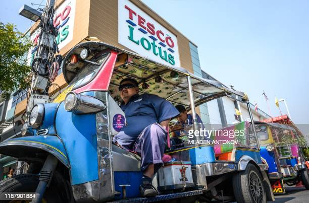 Thailand's traditional Tuk Tuk wait for customers outside a TescoLotus supermarket in Bangkok on December 11 2019 Supermarket chain Tesco Britain's...