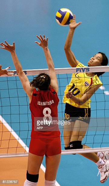 Thailand's Wilavan Apinyapong spikes the ball against the block of Kazakhstan's Korinna Ishimtseva during their match in the final qualifying round...