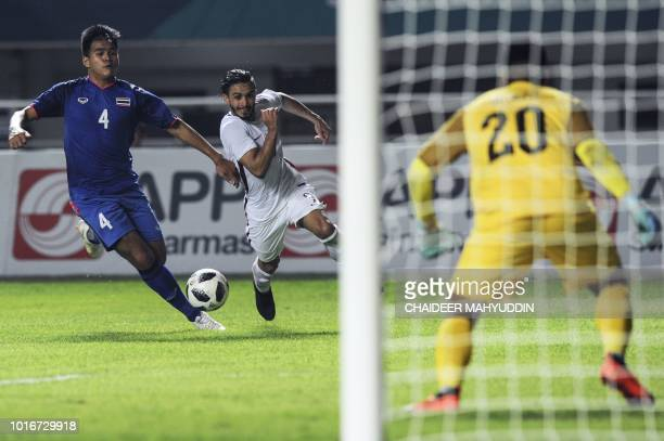 Thailand's Worawut Namvech vies for the ball with Qatar's Meshaal Alshamari during the men's football Group B match between Qatar and Thailand at the...