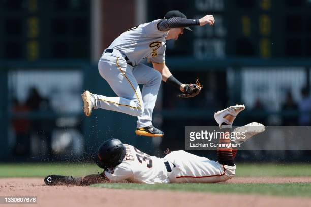 Thairo Estrada of the San Francisco Giants steals second base as Kevin Newman of the Pittsburgh Pirates is unable to catch throw from the catcher,...